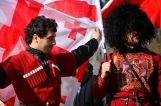 Géorgiens en costume traditionnel devant le drapeau orné de la Croix de Saint-Georges